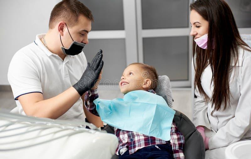 Manlig tandläkare och älskvärd unge, når behandling av att ge sig för tänder som är högt-fem royaltyfri bild