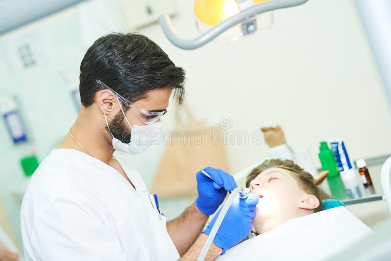 Manlig tandläkare på arbete arkivfoto