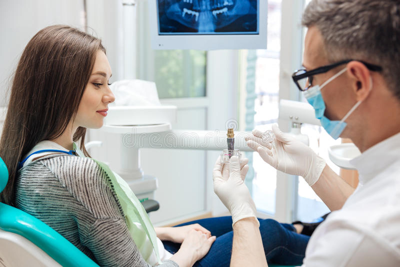Manlig tandläkare som visar hans kvinnliga patient en tand- implantat royaltyfri foto