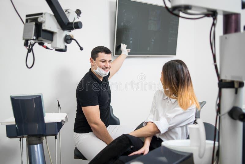 Manlig tandläkare som visar till den kvinnliga patienten hennes tand- röntgenstrålebild på datorbildskärm i den tand- kliniken de royaltyfria foton