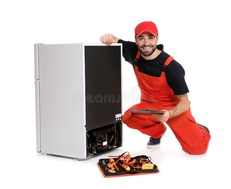 Manlig tekniker med skrivplattan och hjälpmedel nära det brutna kylskåpet på vit arkivfoton