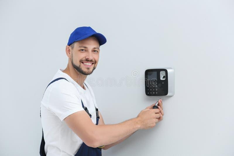 Manlig tekniker som inomhus installerar larmsystemet royaltyfri foto