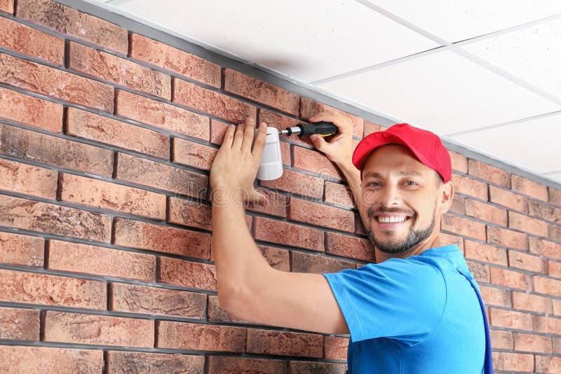 Manlig tekniker som inomhus installerar larmsystemet arkivfoto