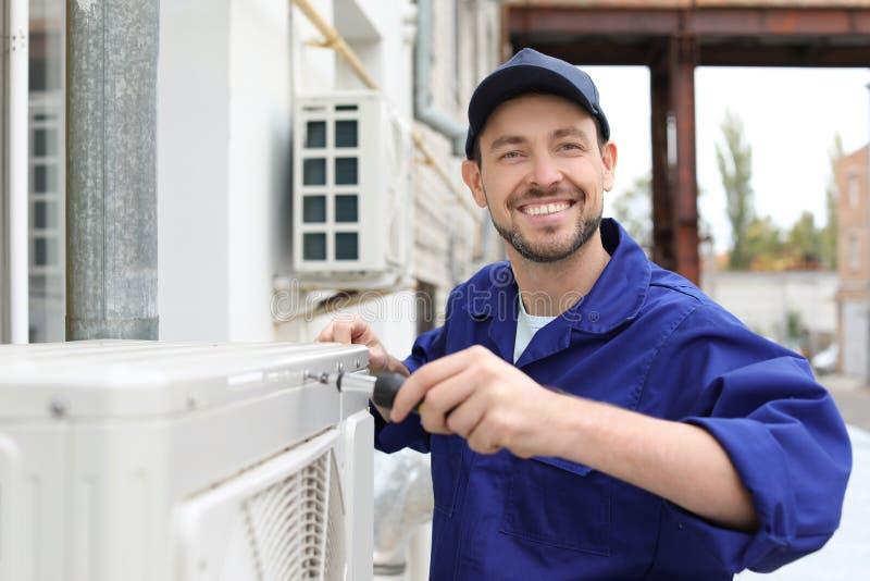 Manlig tekniker som reparerar luftkonditioneringsapparaten royaltyfri bild
