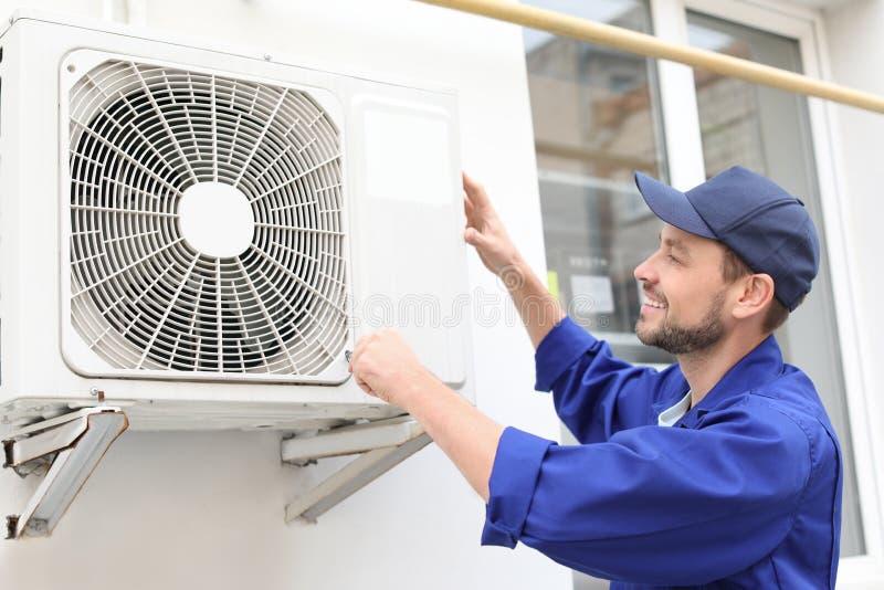 Manlig tekniker som reparerar luftkonditioneringsapparaten royaltyfri foto