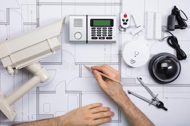 Manlig tekniker Working On Blueprint med säkerhetsutrustningar royaltyfri bild