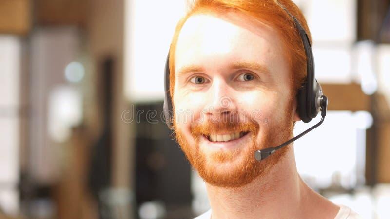 manlig telefonkundtjänstoperatör som är lycklig arkivfoto