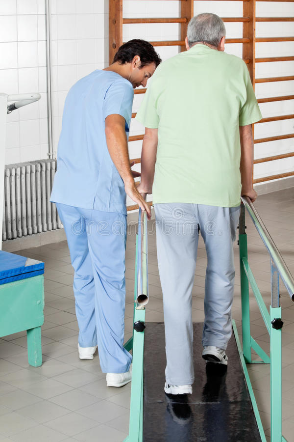 Manlig terapeut Assisting Senior Man som går med royaltyfri foto