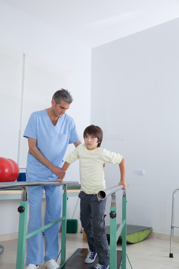 Manlig terapeut med stänger för pojke parallellt royaltyfri foto