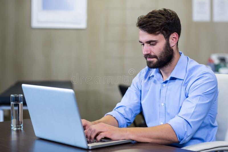 Manlig terapeut som använder bärbara datorn fotografering för bildbyråer