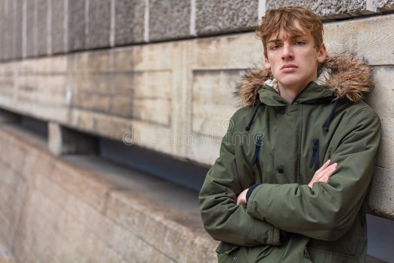 Manlig tonåringpojke för ung man som bär den gröna anoraken arkivfoton