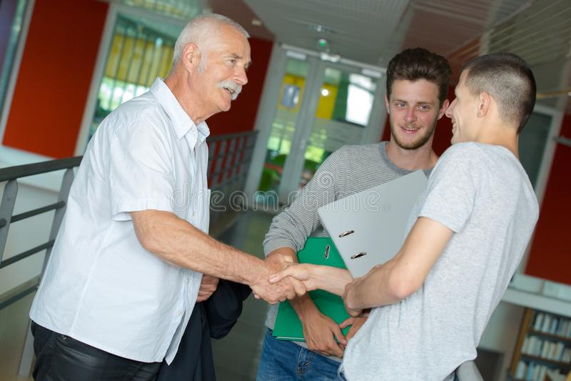 Manlig tonårs- student som skakar handen med läraren royaltyfria bilder