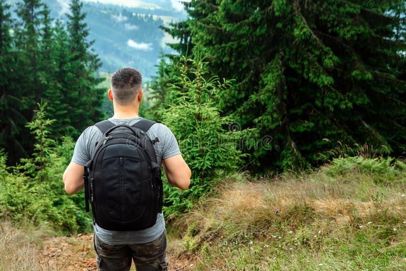 Manlig turist med en ryggsäck som överst står av ett berg som beundrar landskapet Begreppet av aktiva ferier, lopp, arkivfoton