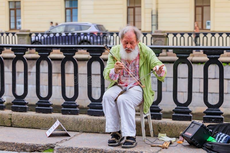 Manlig underhållare i perioddräkt som väntar på turister för fototillfällen nära slottfyrkant i St Petersburg, Ryssland arkivfoto