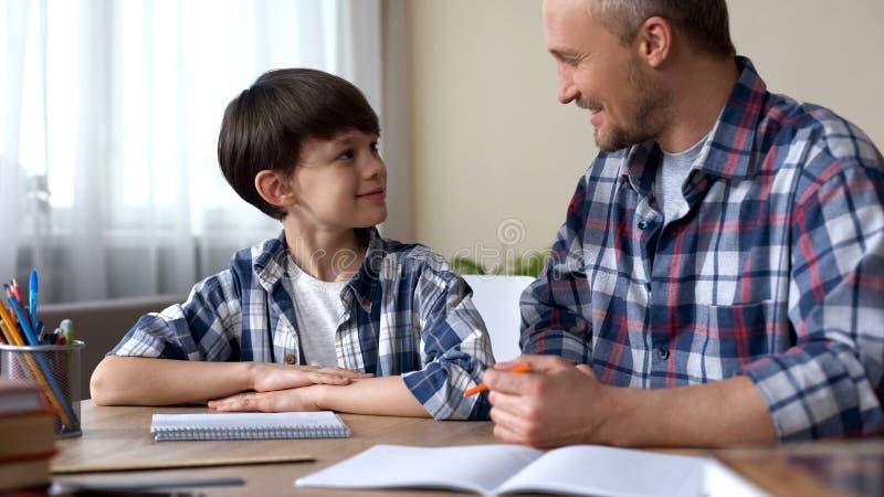 Manlig unge och fader som tillsammans gör läxa och att le till varandra, teamwork royaltyfri foto