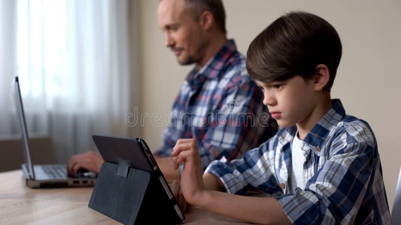 Manlig unge som spelar leken på minnestavlan medan fader som hemma arbetar på bärbara datorn, grej royaltyfri foto