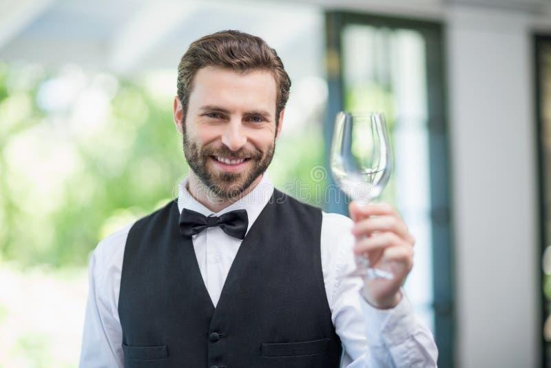 Manlig uppassare som rymmer tomt vinexponeringsglas i restaurangen royaltyfri bild