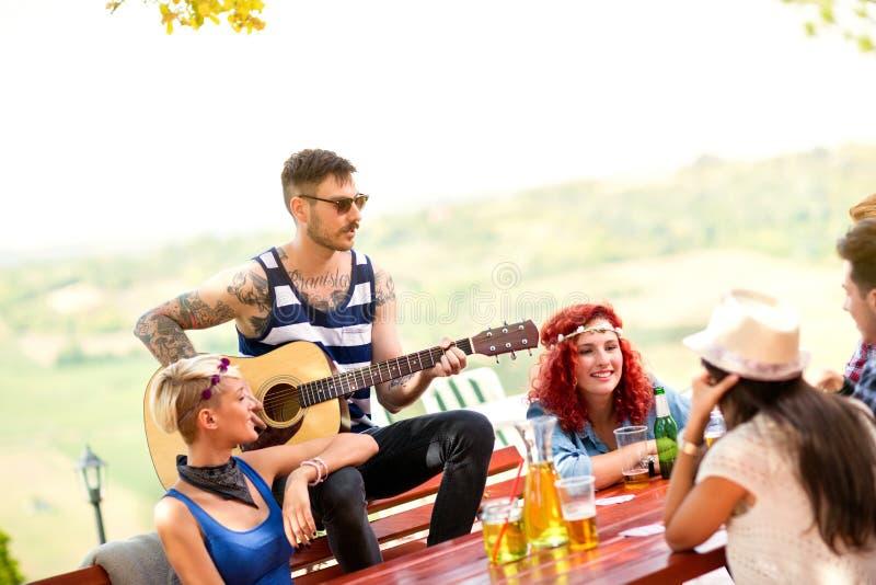 Manlig utomhus- lekgitarr för ung hipster arkivbilder