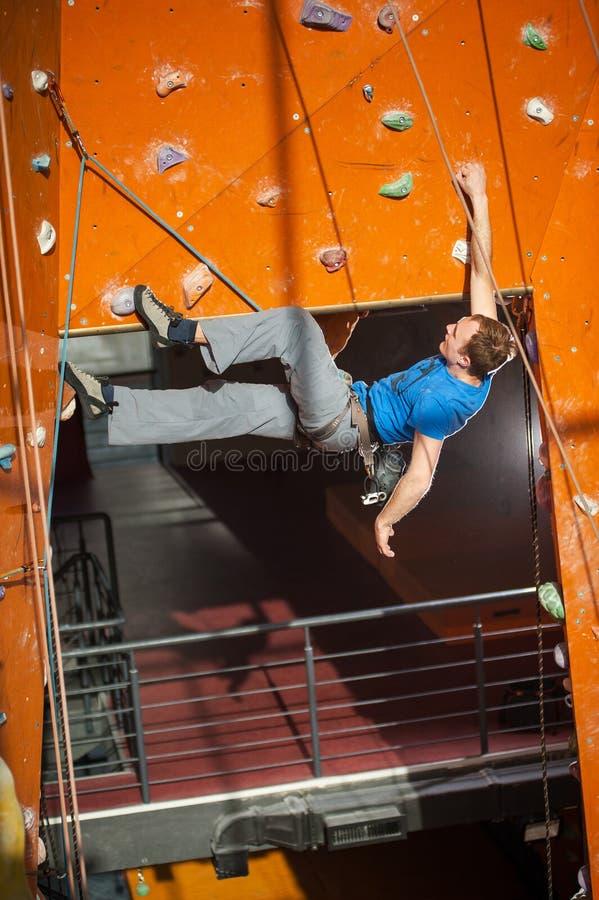 Manlig vagga-klättrare vaggar den praktiserande klättringen på väggen inomhus royaltyfria bilder