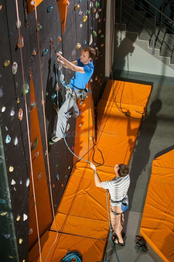 Manlig vagga-klättrare vaggar den praktiserande klättringen på väggen inomhus royaltyfri foto