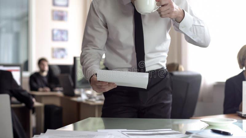 Manlig vd som ser till och med dokumentation och dricker te som st?r i hans kontor royaltyfri foto