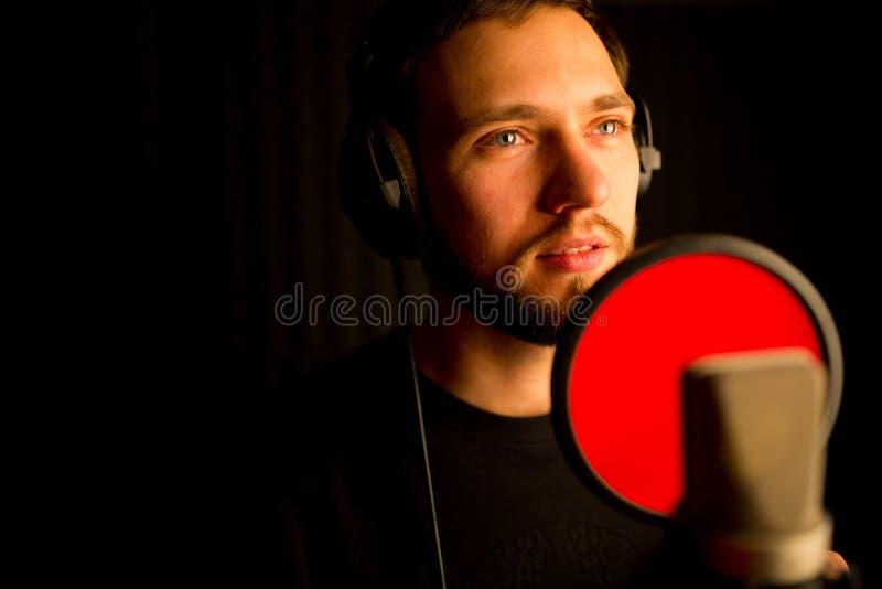 Manlig vokalist som sjunger in i mikrofonen i inspelningstudio Skapa ny hitlåt arkivfoto