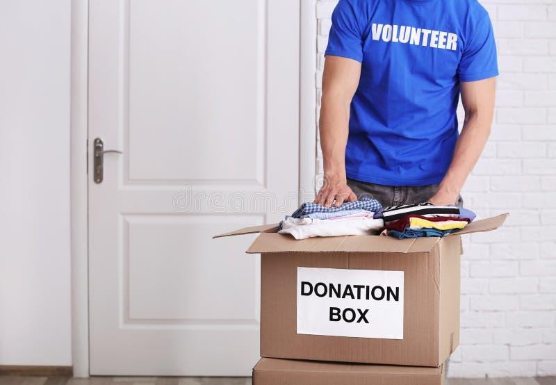 Manlig volontär som sätter kläder i donationask royaltyfri bild
