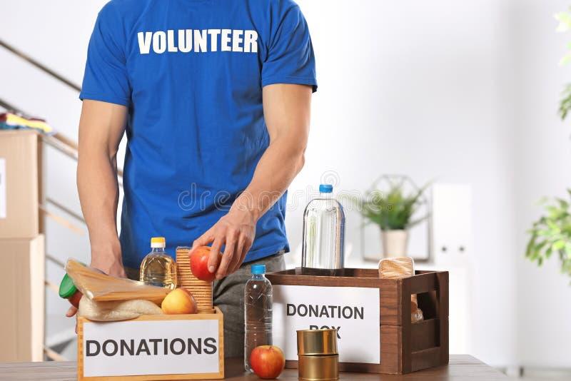 Manlig volontär som sätter livsmedelsprodukter i donationaskar arkivfoton