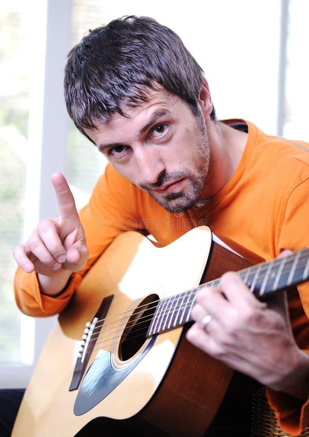 Manlig vuxen spela gitarr arkivbilder