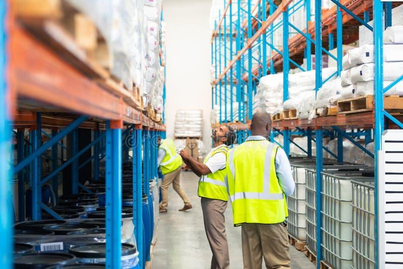 Manliga arbetare som kontrollerar materiel i lager arkivfoto