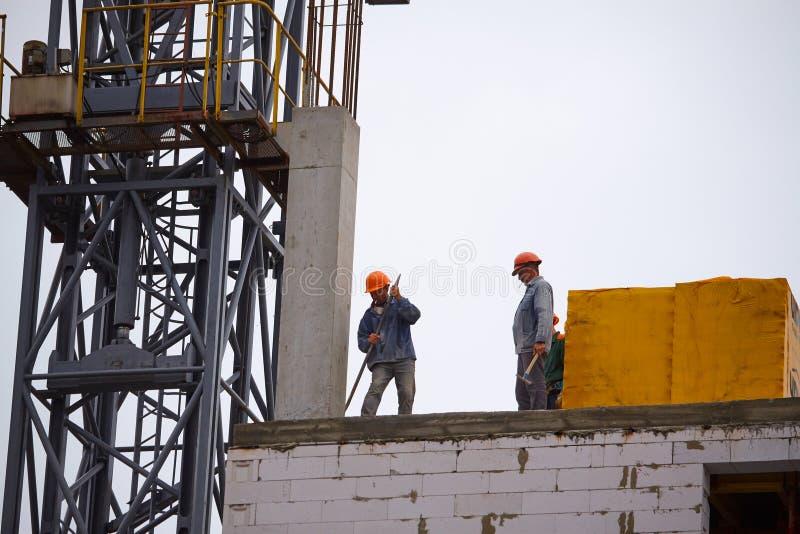 Manliga byggmästare arbetar på konstruktionen av enberättelse cementbyggnad, bildandet av cementservice i fabrikstillverkade dela arkivfoton