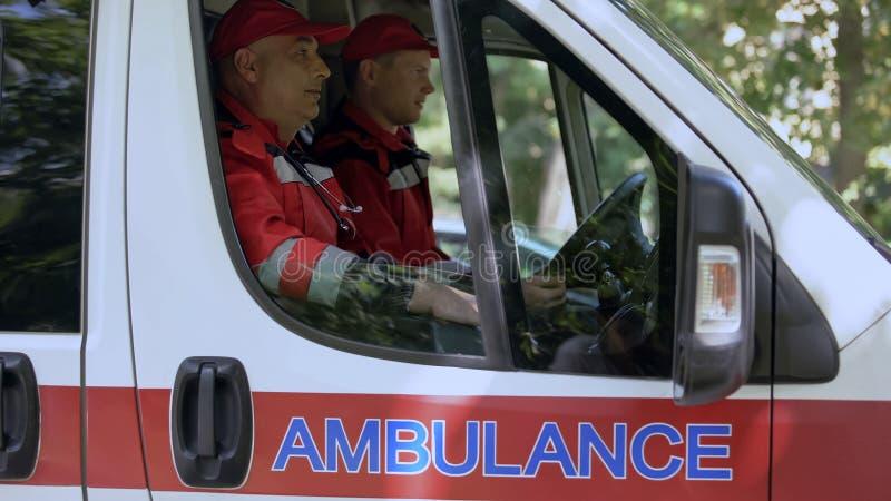 Manliga doktorer som sitter i ambulansen som är klar att köra ut på appellen, professionell royaltyfria bilder