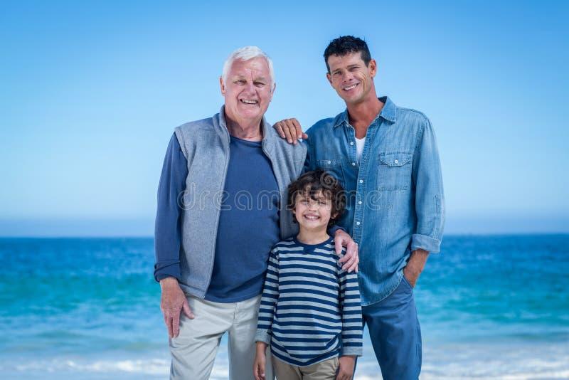 Manliga familjemedlemmar som poserar på stranden arkivfoto