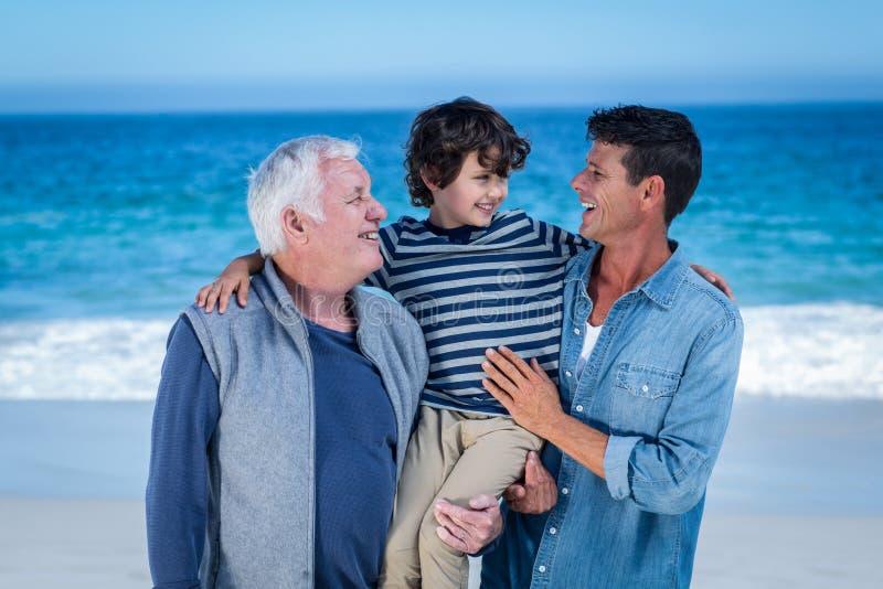 Manliga familjemedlemmar som poserar på stranden arkivbilder