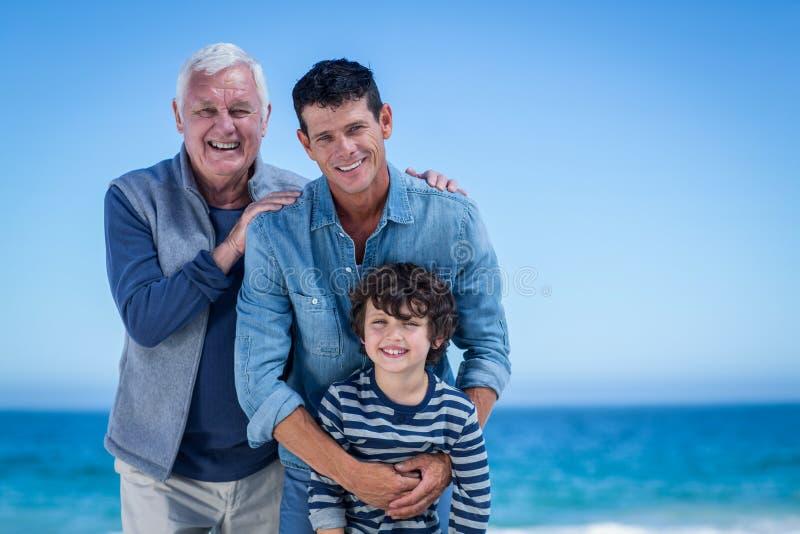 Manliga familjemedlemmar som poserar på stranden royaltyfri fotografi