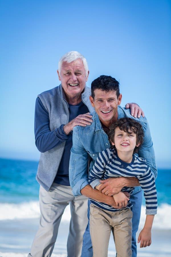 Manliga familjemedlemmar som poserar på stranden fotografering för bildbyråer