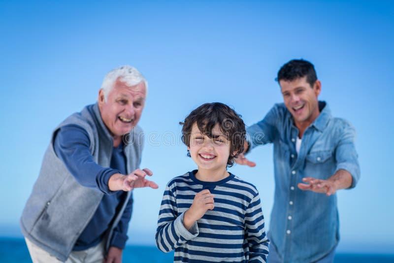 Manliga familjemedlemmar som spelar på stranden arkivfoton