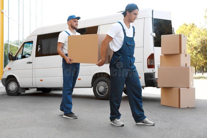Manliga flyttkarlar som lastar av askar från skåpbilen royaltyfria foton