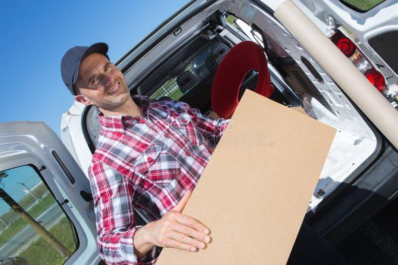 Manliga flyttkarlar som lastar av från lastbilen arkivfoto