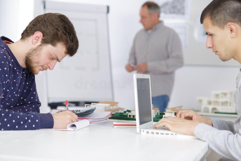 Manliga formgivare som arbetar på bärbar datordatoren på grupp royaltyfri bild