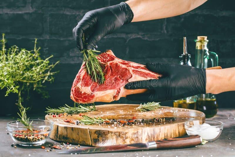 Manliga händer av biff för nötkött för slaktare- eller kockinnehavtomahawk på mörk lantlig köksbordbakgrund arkivbild