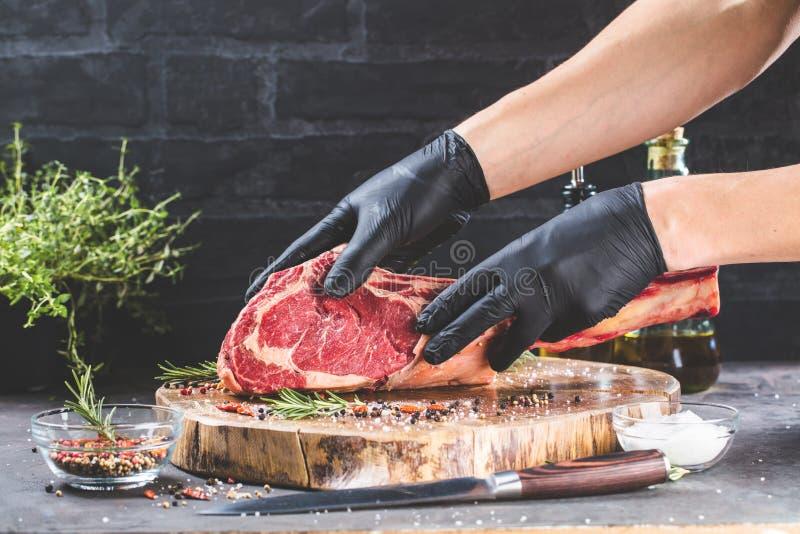 Manliga händer av biff för nötkött för slaktare- eller kockinnehavtomahawk på mörk lantlig köksbordbakgrund arkivbilder