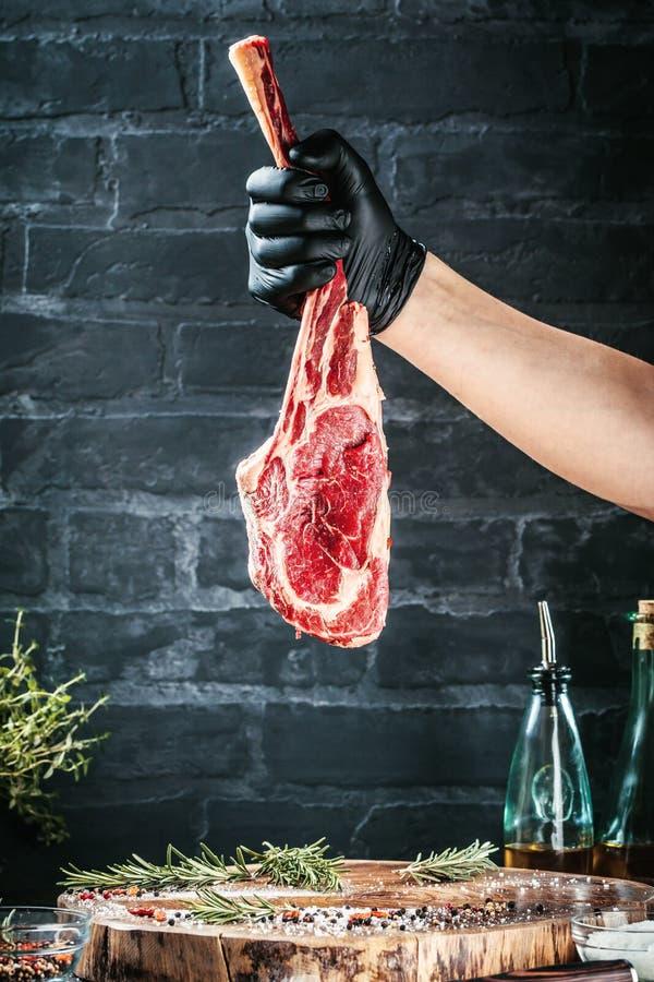 Manliga händer av biff för nötkött för slaktare- eller kockinnehavtomahawk på mörk lantlig köksbordbakgrund royaltyfria foton