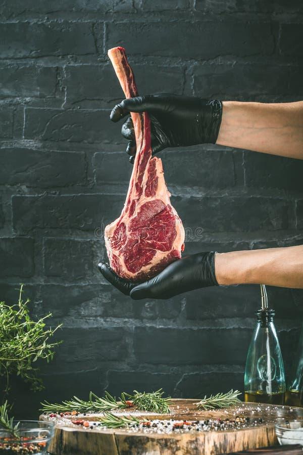 Manliga händer av biff för nötkött för slaktare- eller kockinnehavtomahawk på mörk lantlig köksbordbakgrund royaltyfri bild
