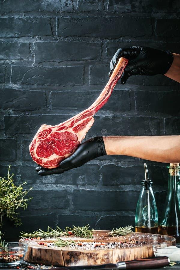 Manliga händer av biff för nötkött för slaktare- eller kockinnehavtomahawk på mörk lantlig köksbordbakgrund arkivfoton