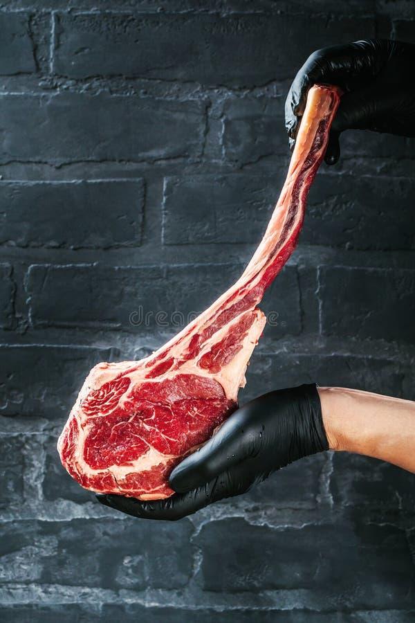 Manliga händer av biff för nötkött för slaktare- eller kockinnehavtomahawk på mörk lantlig köksbordbakgrund arkivfoto