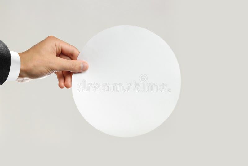 Manliga händer i den vita skjortan och svarta omslaget som rymmer ett vitt ark rundat av papper Isolerat på grå bakgrund closeup arkivfoton