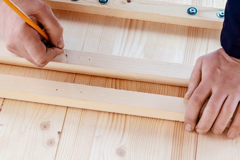 Manliga händer markerar bräden för att borra hål för skruvar arkivbilder