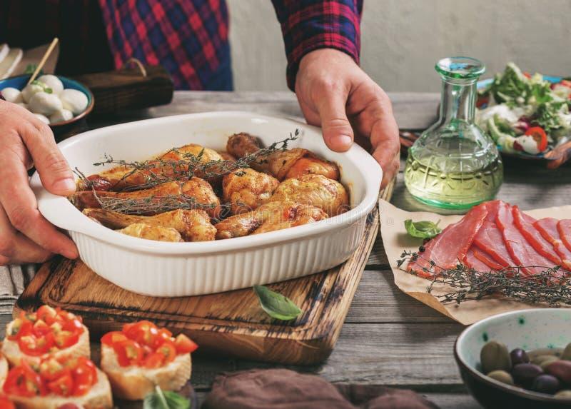 Manliga händer rymmer maträtten med bakade fega ben royaltyfri bild