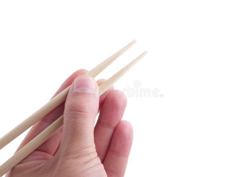 Manliga händer som äter med asiatiska träpinnar som isoleras på vit bakgrund royaltyfria foton